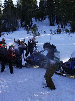 A snowfight breaks out on the mountain trail while a group of Accommodation Tahoe vacationers enjoy a snowmobile tour