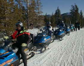 Here geared up and ready to go a group of vacation visitors from Accommodation Tahoe wait to begin their snowmobile adventure.  Snowmobililing is great fun.
